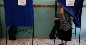 A voter exits a polling booth after marking her ballot slip during the general election, in the suburb of Marousi, Athens, Greece. Photograph: Yorgos Karahalis/Bloomberg
