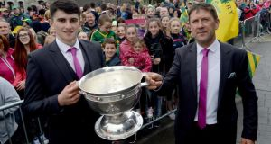 Kerry minor team captain Mark O'Connor and manager Jack O'Connor hold up their All-Ireland trophy at the traditional first stop in Rathmore as both the senior and minor teams arrived back home to Kerry by train. Photograph: Don MacMonagle