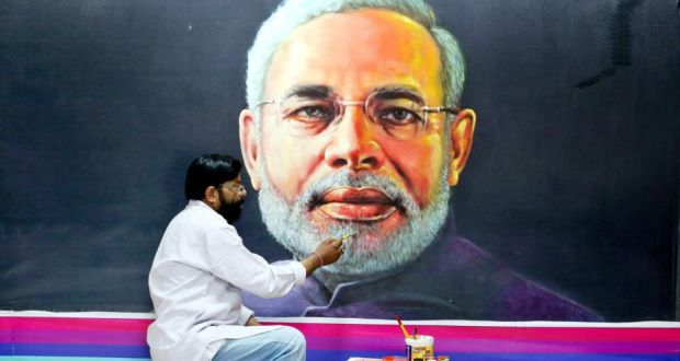 Indian artist Raj Saini puts the finishing touches to a painting  of Indian prime minister Narendra Modi. Photograph: Sanjeev Gupta/EPA
