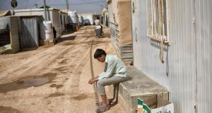 A young Syrian outside his trailer at the Zaatari refugee camp in Jordan. Refugees' resignation and resilience combine with major infrastructure investments to make the place feel ever more like an entrenched city than a makeshift way station. Photograph: Samuel Aranda/The New York Times