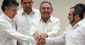 Colombian president Juan Manuel Santos (left) seals the deal in a handshake with  the head of the Farc, Rodrigo Londono, in the presence of   Cuban president Raul Castro.  Photograph: AFP Photo/Getty Images