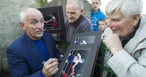 Former WBA Featherweight Champion Barry McGuigan (left) signs autographs before he and champion jockey AP McCoy takes to the track again for a charity donkey derby event in Moneyglass, Co Antrim. Photograph: Liam McBurney/PA Wire.