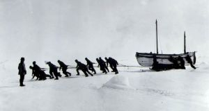 The crew hauling the James Caird, after their ship the Endurance broke up, with Shackleton looking on. Photograph: PA