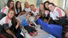 Eoin O'Brien (6), from Shannon, Co Clare, with Cork footballers (L-R) Aisling Hutchings, Sinead Cotter, Ciara O'Sullivan, Brid Stack, Valerie Mulcahy, Roisin Phelan, Aisling Barret and Aine Terry during a visit by the champions to Temple Street Hospital, Dublin. Photograph: Sam Barnes/Sportsfile