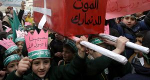 "Children in the West Bank city of Hebron in 2005 with a mock coffin wrapped with a Danish flag that reads, in Arabic, ""Death to Denmark"". Photograph: AFP/Getty Images"
