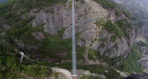 An aerial view shows a glass suspension bridge at the Shiniuzhai National Park in Pinging county, Hunan province, China. The 300-metre long (984 ft) glass bridge, which opened to tourists for the first time last Thursday, spans over a canyon which is about 180-metre-deep. Photograph: Reuters