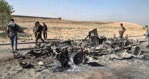Kunduz aftermath: Members of the Afghan security forces pass a burned-out vehicle en route to the centre of Kunduz, Afghanistan. Photograph: EPA