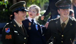 Mary Hannon (10), wearing her great-grandfather's old IRA service medal, with Sgt Amy Hopkins and Lt Stephen Cunningham  at a Defence Forces ceremony at St Raphael's Special School, Celbridge, heralding  the centenary of the 1916 Rising. Photograph: Eric Luke/The Irish Times