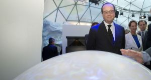 French president Francois Hollande looks on a globe during an exhibition promoting the Climate Change Conference 2015 (COP21). Photograph: Michel Euler/AFP/Getty Images