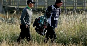Paul Dunne of Ireland walks down the second fairway with his caddie during the third round of the 2015 Alfred Dunhill Links Championship at the Championships Links on October 3, 2015 in Carnoustie, Scotland. Photograph: Mark Runnacles/Getty Images