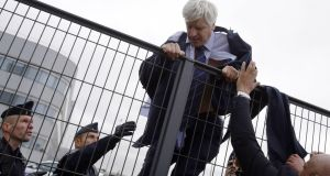 QUICK GETAWAY: Director of Air France in Orly Pierre Plissonnier, nearly shirtless, tries to cross a fence, helped by security and police, after employees invaded Air France offices on Monday over a plan to cut 2,900 jobs. Photograph: Kenzo Tribouillard/ AFP/Getty Images
