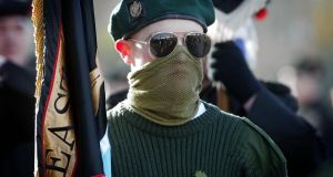 A masked member of the Ulster Defence Association (UDA) colour party at a Remembrance Day service  in  north Belfast, in  2004. Photograph: PA