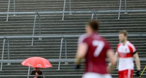 A fan looks on from the terrace during the Round 3B qualifier between Galway and Derry at Pearse Stadium in July. Photograph: Inpho