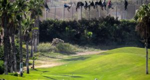 African migrants sit on a border fence above a golf course during an attempt to cross into Spanish territories between Morocco and Spain's north African enclave of Melilla. Photograph: José Palazon/Reuters
