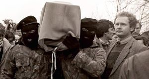 Martin McGuinness with masked IRA men at the funeral of Brendan Burns in 1988. File photograph: Pacemaker