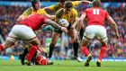 Australia outhalf Bernard Foley is challenged by three Welsh tacklers. Foley kicked all his team's points via five penalties. Photograph:  Billy Stickland/Inpho