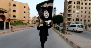 An Isis fighter in Raqqa holds aloft the group's flag. According to Syrians who say Isis tried to recruit them, the group headhunts engineers, offering competitive salaries to those with the requisite experience, and encourages prospective employees to apply to its human resources department.