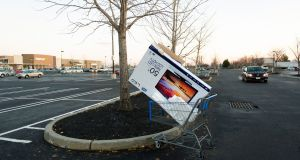 A shopping cart with a discarded box from a big screen TV in the near empty parking lot of a Walmart in Secaucus, New Jersey