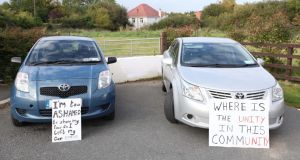 Protest: locals parked cars to block the six-month halting site proposed for Rockville Drive in Carrickmines; the placards were left by counterprotesters. Photograph: Stephen Collins/Collins