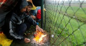 Migrants burn shoes in a bonfire to warm themselves up as they wait at the border with Slovenia in Trnovec, Croatia, on Monday. Photograph: Reuters