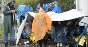 Migrants take cover from the rain as they wait at the Croatian-Slovenian border in Trnovec to cross into Slovenia on Monday. Photograph: AFP