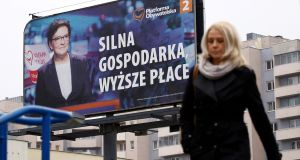 A woman walks by an election billboard in Warsaw featuring Poland's prime minister Ewa Kopacz,  whose ruling PO party is trailing in polls. Photograph: Kacper Pempel/Reuters