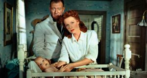 American actor John Wayne  and  Maureen O'Hara looking after a child in 'The Wing of Eagles' from 1957. Photograph:   Mondadori Portfolio by Getty