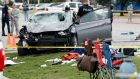 Police investigate a damaged car after the vehicle crashed into a crowd of spectators during the Oklahoma State University homecoming parade.