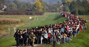 Migrants are escorted through fields by Slovenian police and the army as they walk from the village of Rigonce to Brezice refugee camp on Saturday. Photograph: Jeff J Mitchell/Getty Images
