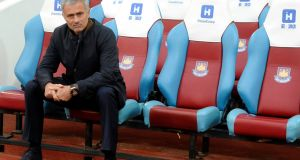 José Mourinho sits on his own before the start of the English Premier League game between West Ham United and Chelsea. Photograph: Hannah McKay/EPA