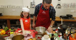 Damian Cullen helps his five-year-old daughter – or maybe more accurately Eve helps her father – to make 'Bangin' Burritos with Steak and Mexican Rice' at Dublin's Cooks Academy as part of 'Cook Along with Ben's Beginners', which promotes children and parents cooking together. Photograph: Robbie Reynolds