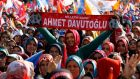 "A supporter of the ruling AK Party holds a scarf with a slogan that reads, ""Man of the nation – Ahmet Davutoglu"", in reference to the prime minister, during an election rally in the central Anatolian city of Konya, on Friday. Photograph: Umit Bektas/Reuters"