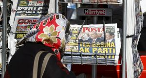 A woman looks at newspapers at a kiosk in Istanbul, Turkey, saying 'AK Party on its own' after president Tayyip Erdogan's party   won almost 50 per cent of the vote in a snap  election. Photograph: Osman Orsal/Reuters.