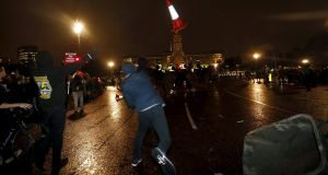 A supporter of the activist group Anonymous throws a traffic cone towards  police officers outside Buckingham Palace during a protest in London. Photograph: Reuters