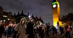 Masked protesters pass in front of the Houses of Parliament during the Million Mask March. Photograph: Photograph: Getty