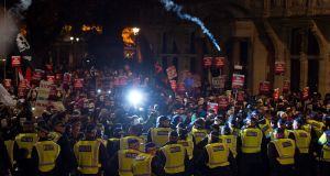 Masked protesters are stopped by a police line during the Million Mask March on Thursday night  in London. The annual anti-establishment protest is organised by activist group Anonymous. Photograph: Getty