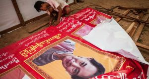 Volunteers take down posters of Aung San Suu Kyi at the National League for Democracy  head office  in Kaw Hmu, Burma,  ahead of Sunday's landmark election. Photograph:  Lauren DeCicca/Getty Images