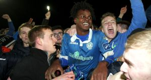 Finn Harps'  BJ Banda is swamped by fans at the final whistle after his goal secured Premier Division football for the Donegal  club in their play-off against Limerick at Finn Park in Ballybofey. Photograph: Lorcan Doherty/Inpho/Presseye