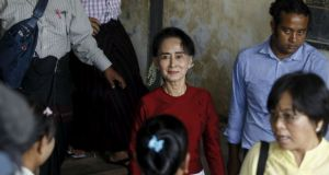 Burma pro-democracy leader Aung San Suu Kyi smiles to supporters as she visits polling stations at her constituency Kawhmu township. Photograph: Reuters