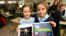 Twins Shayna and Orlaith Teggart, pupils at St Hugh's National School in Dowra,  with a proof of the cover of The Scrapbook of Regrets. Photograph: Brian Farrell