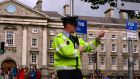 A garda directing traffic on Dublin's College Green. Plans for the redesign of the area, including a permanent ban on private cars and a new pedestrian plaza in front of the Bank of Ireland, will be presented to Dublin city councillors later. Photograph: Cyril Byrne/The Irish Times.