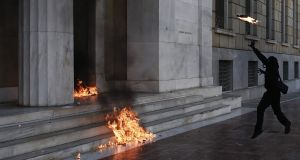 A protester throws a fire bomb at the entrance to Greece's central bank during a 24-hour general strike in Athens on Thursday. Photograph: Kostas Tsironis/Bloomberg