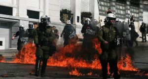 Riot policemen walk by fires caused by petrol bombs thrown by youths following clashes between police and protesters in central Athens. Photograph: Alkis Konstantinidis/Reuters