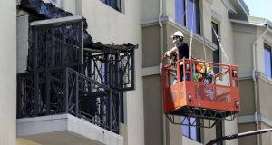 Workmen examine the damage at the scene at the Berkeley balcony collapse in California that killed six student and seriously injured seven others. Photograph: Elijah Nouvelage/Reuters