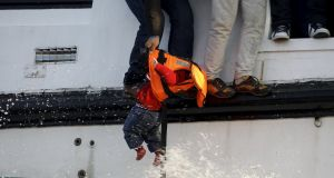 A refugee prepares to hand over a toddler to a volunteer lifeguard off Lesbos. Photograph: Giorgos Moutafis/Reuters