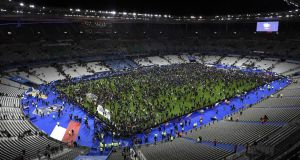 Spectators gather on the pitch of the Stade de France  after explosions were heard outside the  stadium. Photograph: Franck Fife/AFP/Getty Images