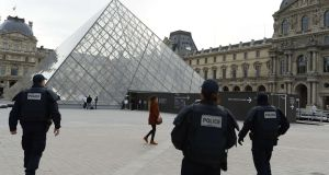Police patrol in front of the Louvre Pyramid. Photograph: Bertrand Guay/AFP Getty
