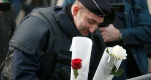 A policeman places flowers outside the Bataclan concert hall after the attacks in Paris. Photograph: Charles Platiau/Reuters