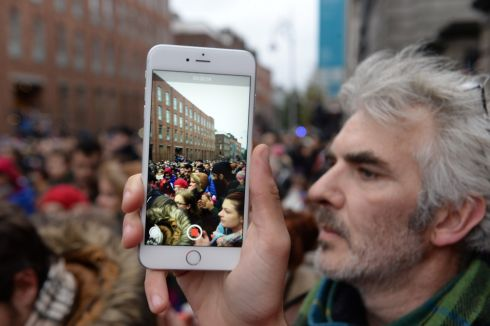 Taking photos by phone of a segment of the Dublin marchers. Photograph: Cyril Byrne: The Irish Times