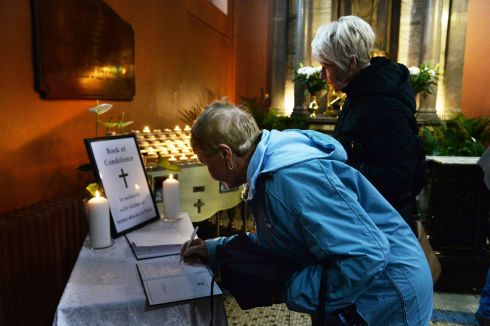 People signing a book of condolences  at the Pro-Cathedral  in Dublin following Mass on Saturday. Photograph: Cyril Byrne: The Irish Times